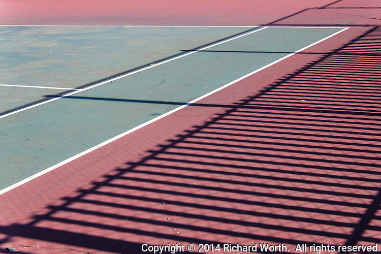 White lines on a tennis court green.  Out of bounds red decorated with shadow lines painted by the sun and a fence.