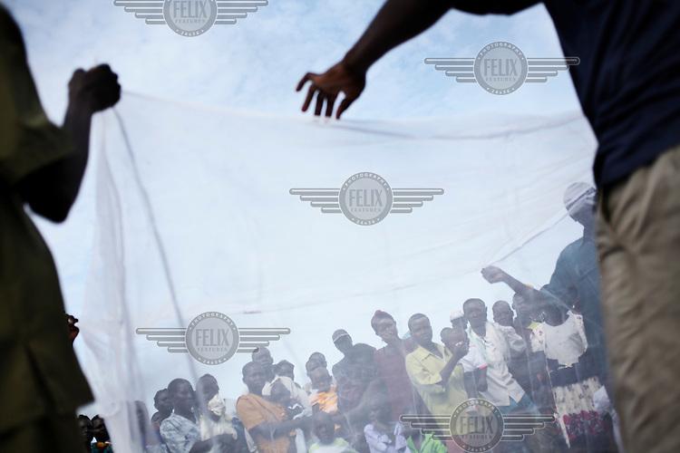 A free mosquito net distribution near Masindi.