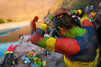 "A Cora Indian man, painting his body in colors, prepares himself for the religious ritual ceremony of Semana Santa (Holy Week) in Jesús María, Nayarit, Mexico, 22 April 2011. The annual week-long Easter festivity (called ""La Judea""), performed in the rugged mountain country of Sierra del Nayar, merges indigenous tradition (agricultural cycle and the regeneration of life worshipping) and animistic beliefs with the Christian dogma. Each year in the spring, the Cora villages are taken over by hundreds of wildly running men. Painted all over their semi-naked bodies, fighting ritual battles with wooden swords and dancing crazily, they perform demons (the evil) that metaphorically chase Jesus Christ, kill him, but finally fail due to his resurrection. La Judea, the Holy Week sacred spectacle, represents the most truthful expression of the Coras' culture, religiosity and identity."