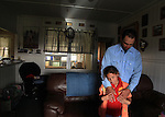 "Hawaiian cowboy, Wayne Tachera and his daughter, Nahe, 9, share a tender moment at their home on Kahua Ranch in North Kohala, Hawaii. The house is part of ""cowboy housing"" which is subsidized by the ranch as part of a cowboy's benefit package. ""We get free housing, free electricity, free water.  It makes up for cowboy pay because cowboy pay is not much at all"","" says Tachera.  Nahe and her sister, Kamehana, are very close to their father who taught them to ride horses as toddlers and took them to work with him when childcare wasn't available."