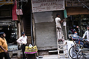 Pedestrians walk past a worker painting a jewellery stores in Dariba Kalan, Old Delhi, India. Photo: Sanjit Das/Panos Pictures