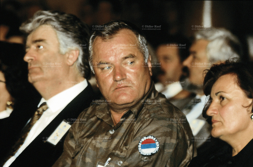 "Yougoslavia. Bosnia. Serbian republic. Bijelina. Radovan Karadzic (L). Ratko Mladic (R) and his wife. Celebration for ""Vidovdan"" day. Each year on the 28th of June, the serbs celebrate the day of the army. Religious service in the orthodox church. Radovan Karadzic was arrested in Belgrade on 21 July 2008. He was extradited to the Netherlands, and is currently in The Hague, in the custody of the International Criminal Tribunal for the former Yugoslavia. General Ratko Mladic is on the list of the International Criminal Tribunal for the former Yugoslavia (ICTY), based in The Hague in the Nederlands, as a most wanted man for war crimes. © 1995 Didier Ruef"