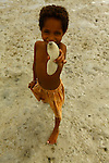 A little girl show a sea cucumber in the village of Hessessai Bay at PanaTinai (Panatinane)island in the Louisiade Archipelago in Milne Bay Province, Papua New Guinea.  The island has an area of 78 km2..The Louisiade Archipelago is a string of ten larger volcanic islands frequently fringed by coral reefs, and 90 smaller coral islands located 200 km southeast of New Guinea, stretching over more than 160 km and spread over an ocean area of 26,000 km? between the Solomon Sea to the north and the Coral Sea to the south. The aggregate land area of the islands is about 1,790 km? (690 square miles), with Vanatinai (formerly Sudest or Tagula as named by European claimants on Western maps) being the largest..Sideia Island and Basilaki Island lie closest to New Guinea, while Misima, Vanatinai, and Rossel islands lie further east..The archipelago is divided into the Local Level Government (LLG) areas Louisiade Rural (western part, with Misima), and Yaleyamba (western part, with Rossell and Tagula islands. The LLG areas are part of Samarai-Murua District district of Milne Bay. The seat of the Louisiade Rural LLG is Bwagaoia on Misima Island, the population center of the archipelago.PanaTinai (Panatinane) is an island in the Louisiade Archipelago in Milne Bay Province, Papua New Guinea. The island has an area of 78 km2..The Louisiade Archipelago is a string of ten larger volcanic islands frequently fringed by coral reefs, and 90 smaller coral islands located 200 km southeast of New Guinea, stretching over more than 160 km and spread over an ocean area of 26,000 km? between the Solomon Sea to the north and the Coral Sea to the south. The aggregate land area of the islands is about 1,790 km? (690 square miles), with Vanatinai (formerly Sudest or Tagula as named by European claimants on Western maps) being the largest..Sideia Island and Basilaki Island lie closest to New Guinea, while Misima, Vanatinai, and Rossel islands lie further east..The archipelago is divided into the Local