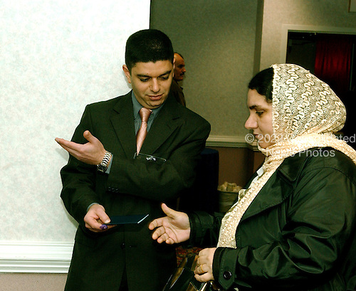 McLean, VA - December 13, 2005 -- Fatima Youssif, right, who emigrated to Binghamton, New York from Duhua, Iraq to escape being gassed by Saddam Hussein, is invited to vote by an unidentified poll worker in the Iraqi election in McLean, Virginia on December 13, 2005. .Credit: Ron Sachs / CNP.(RESTRICTION: NO New York or New Jersey Newspapers or newspapers within a 75 mile radius of New York City)