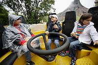 Italy. Province of Veneto. Castelnuovo del Garda. A mother, wearing a plastic raincoat as water protection, and her two children Nicola and Micaela Ruef are riding down the attraction: Jungle rapids. Smoking volcano in the back. Gardaland is the biggest amusement park in Italy and one of the largest in the whole of Europe. MODEL RELEASED. © 2006 Didier Ruef