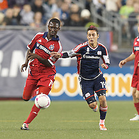 Chicago Fire midfielder Patrick Nyarko (14) brings the ball forward as New England Revolution midfielder Diego Fagundez (14) closes. In a Major League Soccer (MLS) match, the New England Revolution (blue) defeated Chicago Fire (red), 1-0, at Gillette Stadium on October 20, 2012.