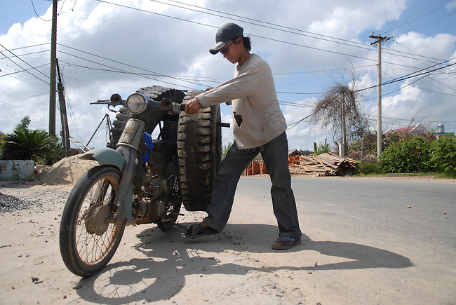 A Vietnamese man loads truck tired on to his motor bike for transport outside of Ho Chi Minh City, Vietnam.