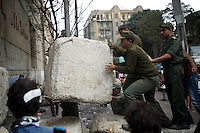 Army men build up a concrete barricade to prevent protestors to access the security forces positions in central Cairo.