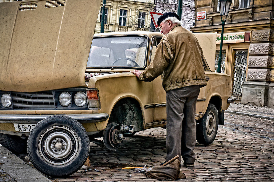 PRAGUE, CZECH REPUBLIC - MARCH 18th 2011: Senior resident of Prague fixing an old card in the street. Photo taken march 18 2011. Editorial Use Only.