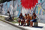 Central America, Cuba, Havana. Local girls on bench in Muraleando neighborhood.