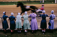 Accustomed to the pace of horse-drawn huggles and plows, Amish women watch a professional harness racer blur past on a half-mile track. They later cheer as Amish men take up the reins for a high-wheel cart challenge that highlights the race card at Ohio's Geuaga County Fair.