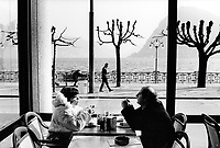 Switzerland. Ticino. Lugano. A couple eats a snack in a café near the lake on a sunny spring day. © 2003 Didier Ruef