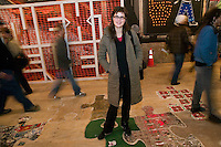15 December 2006 - New York City, NY - Artist Gaetane Michaux (C) poses for the photographer standing on her artwork &quot;Build'in Pieces - No Heels&quot; as people walk through a three-day street art exhibition held in a 19th-century brick building at 11 Spring Street in the NoLIta neighborhood of New York City, USA, 15 December 2006. The building's new owners, Caroline Cummings and Bill Elias, called on the Wooster Collective to curate the show as a last hurrah for a site that long served as a canvas for street art.<br />