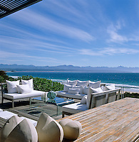 View over the Indian Ocean from the comfortable white upholstered benches on the teak decking which overlooks the beach