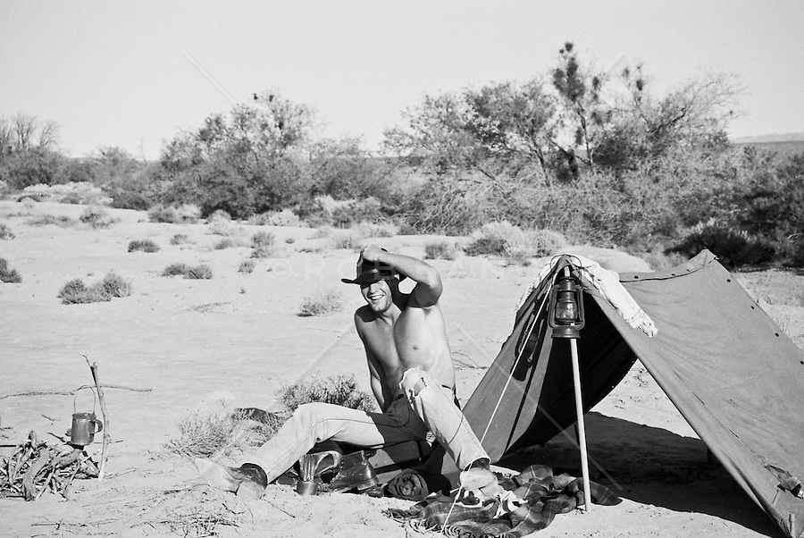 Laughing man in a cowboy hat laughing by a pup tent in the desert