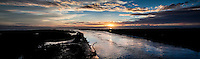 Swollen by recent rains, San Lorezo Creek makes its way to San Francisco Bay at sunset.  A multiple image panoramic.