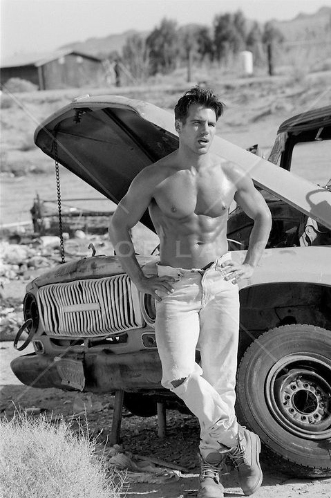 sexy shirtless man by an old truck in the California desert