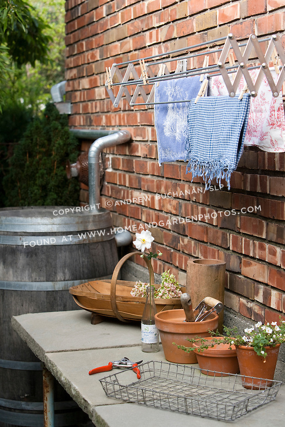 A rain barrel captures water for use in the garden, while a stone potting bench provides space for gardening projects in the side yard of a Seattle home.