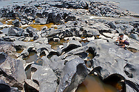 A Llanero plainsman scopes out interesting pebbles in a volcanic boulder field in the the middle of the Orinoco River - Orinoco River Basin - Venezuela/Colombia border - South America