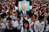 Mourners react as the coffin of former king Norodom Sihanouk arrives to the Royal Palace in Phnom Penh October 17, 2012. Tens of thousands poured into Cambodia's capital to witness the procession on Wednesday of the body of Sihanouk, a revered figure who ruled through the triumph of independence to the tragedy of its brutal civil war. Mourners dressed in white lined the 10-km (6-mile) route to welcome the return of Sihanouk, the flamboyant former monarch who died at 89 of heart failure on Monday in Beijing, his residence since abdicating eight years ago. REUTERS/Damir Sagolj (CAMBODIA)
