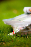 stack of magazines in the grass