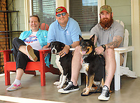 NWA Democrat-Gazette/ANDY SHUPE<br /> Angie Pratt (left), executive director of Soldier On Soldier Dogs, poses Thursday, May 14, 2015, with veterans Josh Alison (center) and his service dog, Elizabeth; and Spencer Offenbacker and his service dog, Dewi; at the organization's Fayetteville office. The organization is a non-profit organization that provides service dogs for veterans with post-traumatic stress disorder and pairs volunteers with foster dogs to train.