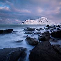 Rocky coastline of Flakstadøy with Hustind mountain peak in background, near Flakstad, Flakstadøy, Lofoten Islands, Norway