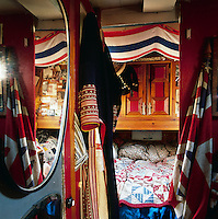 The cosy sleeping area in the houseboat has a red, white and blue theme