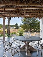 An outdoor dining area on the covered terrace with series of four weathered folding chairs and a rustic table with a circular concrete top and wooden base