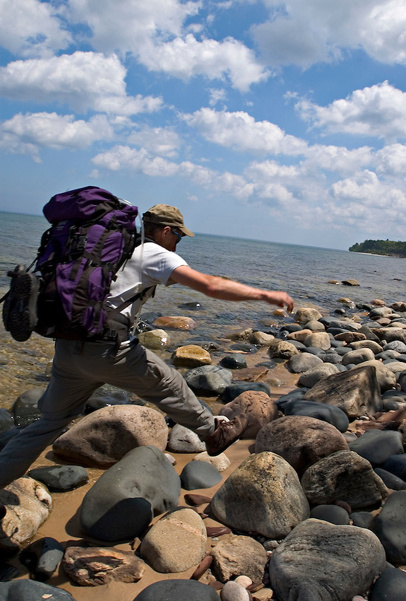 A backpacker jumps on cobblestones near Au Sable Point in Pictured Rocks National Lakeshore near Grand Marais, Mich.
