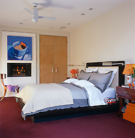 The contemporary bedroom is simply furnished with a built-in wardrobe of pale wood and a wall-mounted gas fire