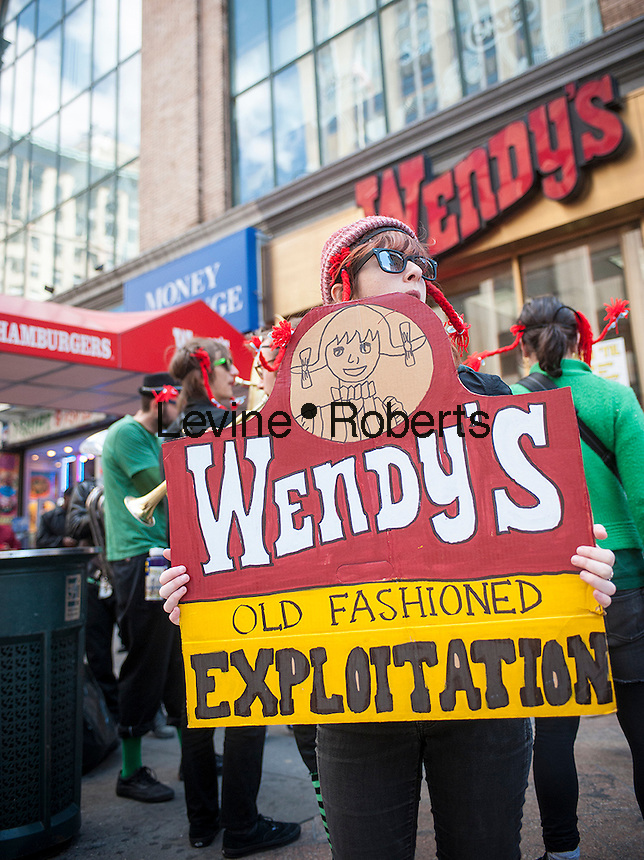 Members of the Community Farmworker Alliance and their supporters dress up in pigtail costume to protest in front of a Wendy's fast food restaurant in Midtown Manhattan in New York on Sunday, April 14, 2013. The group is pressuring Wendy's to sign onto the Fair Food Agreement where food companies will not use produce that has been picked by workers paid sub-standard wages and exposed to other exploitation. A number of companies such as Trader Joe's, Taco Bell (Yum! Brands) and McDonald's have signed the agreement.  (© Richard B. Levine)