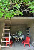 Two red bench seats are placed either side of a metal table in a covered terrace space.