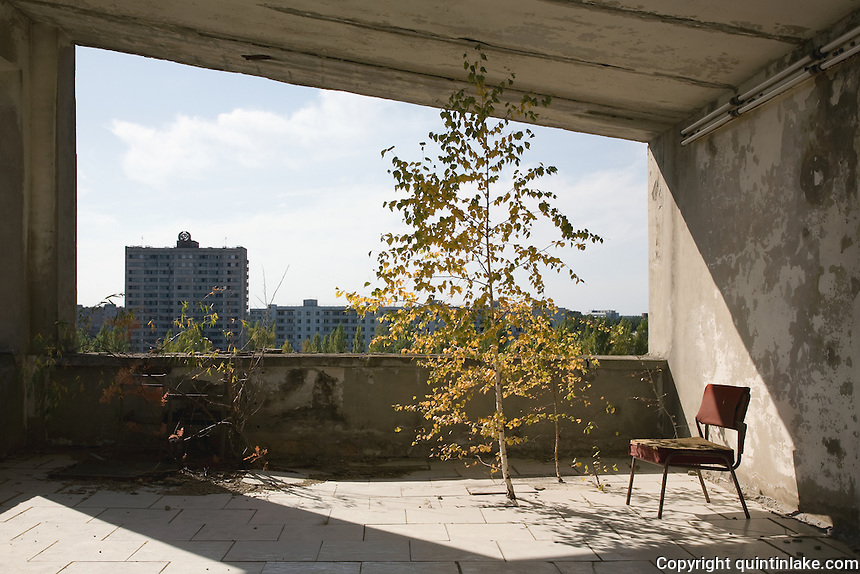 A silver birch tree grows through the floor on the terrace of Hotel Polissia. The hammer and sickle is visable atop the distant appartments.<br /> <br /> Pripyat (Pripiat), 1km from the reactor, was designed as an exemplar of Soviet planning for the 50,000 people who worked at the Chernobyl Nuclear Power Plant in 1986 the result was the worst nuclear accident in history. Now a ghost town in Ukraine, Pripyat is in a radioactive exclusion zone unfit for human habitation for hundreds of years. This image was taken in 2007 over 5 hours, apparently the safe period of exposure.<br /> <br /> This image was exhibited at the Architectural Association, London in the exhibition &quot;Pripyat: 21 Years After Chernobyl, photographs by Quintin Lake&quot; 2008<br /> <br /> The image is also published in the book &quot;Drawing Parallels, Architecture Observed&quot; by Quintin Lake