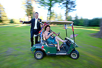 Champagne in hand, a groom hangs off the back of a golf card as they take a joyride around the course. (Photo by Scott Eklund/Red Box Pictures)