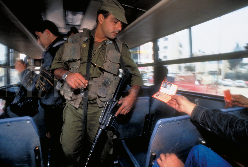 TITLE - DISTANT RELATIONS, ISRAELI SOLDIER EYES PALESTINIAN'S IDENTIFICATION PAPERS AT A SECURITY CHECKPOINT,. JERUSALEM ISRAEL.