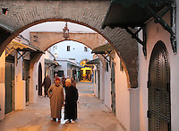 Men wearing djellabas walking in a narrow street under archways in the medina or old town of Tetouan, on the slopes of Jbel Dersa in the Rif Mountains of Northern Morocco. Tetouan was of particular importance in the Islamic period from the 8th century, when it served as the main point of contact between Morocco and Andalusia. After the Reconquest, the town was rebuilt by Andalusian refugees who had been expelled by the Spanish. The medina of Tetouan dates to the 16th century and was declared a UNESCO World Heritage Site in 1997. Picture by Manuel Cohen