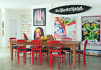 The walls of the dining room are covered in a collection of bold, slightly punky artwork and the chairs are painted in a lipstick-red lacquer
