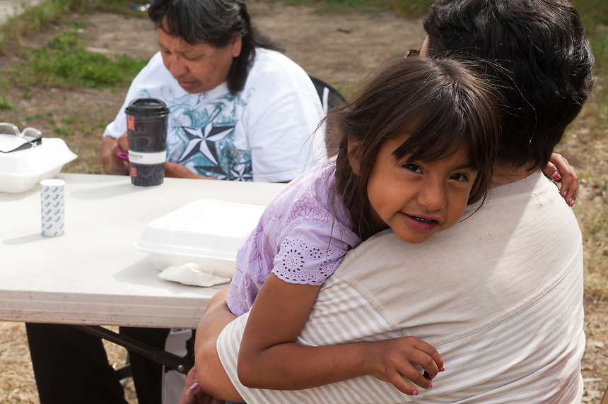 Tatum Old Crow, 5, gets a hug from adopted mother Vanessa Little Light while having breakfast with friends on the Crow Reservation at Crow Agency, Montana, Thursday, May 16, 2013. Pending new ports for shipment to Asia through either the U.S. or Canada, Cloud Peak Energey hopes to open new high-grade coal mines on and near the Crow Reservation in southern Montana. The tribe is equally hopeful the new mines would bring long-awaited economic stability to the tribe. (Kevin Moloney for the New York Times)