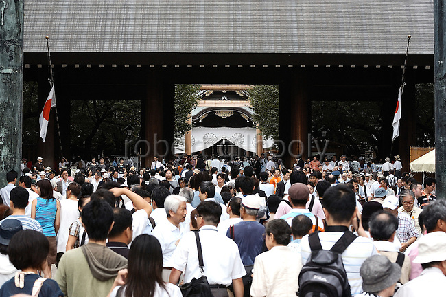 Thousands of people line up to pray on the anniversary of the end of WWII at Yasukuni Shrine in Tokyo, Japan. Every year on August 15, the day Japan officially surrendered in WWII, tens of thousands of Japanese visit the controversial shrine to pay their respects to the 2.46 million war dead enshrined there, the majority of which are soldiers and others killed in WWII and including 14 Class A convicted war criminals, such as Japan's war-time prime minister Hideki Tojo. Each year speculation escalates as to whether the country's political leaders will visit the shrine, the last to do so being Junichiro Koizumi in 2005. Nationalism in Japan is reportedly on the rise, while sentiment against the nation by countries that suffered from Japan's wartime brutality, such as China, has been further aggravated by Japan's insistence on glossing over its wartime atrocities in school text books...Photographer:Robert Gilhooly..