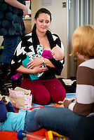 A mother breastfeeds her baby while talking to another mother at a drop-in breastfeeding support centre.<br /> <br /> Image from the breastfeeding collection of the &quot;We Do It In Public&quot; documentary photography picture library project: <br />  www.breastfeedinginpublic.co.uk<br /> <br /> Hampshire, England, UK<br /> 13/03/2013<br /> <br /> &copy; Paul Carter / wdiip.co.uk