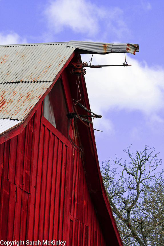 A red, wood barn with a corrugated metal roof near Calistoga in Napa County in Northern California.