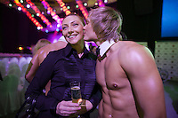 Moscow, Russia, 24/10/2009..A male stripper kisses a visitor to the Millionaire Fair in Moscow. The event has become an annual fixture, attracting thousands of would-be and existing Russian millionaires to view and purchase a wide range of luxury goods. This year however the fair was much smaller, an indication of how the formerly booming Russian economy has been hit by the world financial crisis.