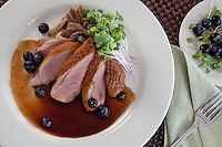 Pan Seared Duck Breast and Duck Confit: truffle potato pur&eacute;e, blueberry-Madeira sauce, micro greens<br />
