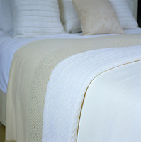 A welcome relief from the ubiquitous duvet this double bed has been dressed in woollen blankets in white and oatmeal