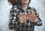 woman lies in bed and reach out with hands