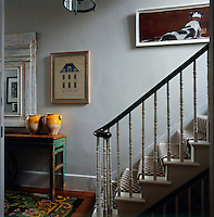 In the hallway, the original period staircase has been painted white and the banister left as polished wood. Several artworks and pottery urns are displayed