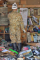April 1st, 2011, Miyako, Japan - A man in a camouflaged coverall checks the calendar as he cleans up the mess  left by a tidal wave in Miyako City, Iwate Prefecture, on April 1, 2011, three weeks after the city was devastated by a magnitude 9.0 earthquake and ensuing tsunami. (Natsuki Sakai/AFLO) [3615] -mis-...