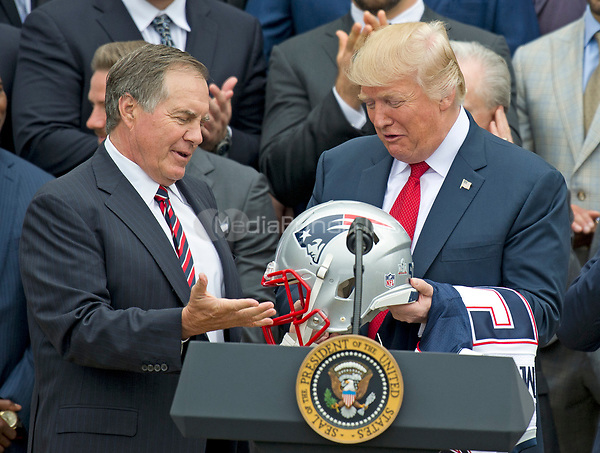 New England Patriots head coach Bill Belichick, left, presents a team helmet to United States President Donald J. Trump, right, after making remarks during the ceremony welcoming the Super Bowl Champions to the South Lawn of White House in Washington, DC on Wednesday, April 19, 2917.  <br /> Credit: Ron Sachs / CNP/MediaPunch<br /> <br /> (RESTRICTION: NO New York or New Jersey Newspapers or newspapers within a 75 mile radius of New York City)