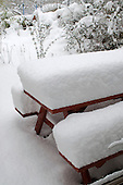 Winter snow piled high on the picnic table.
